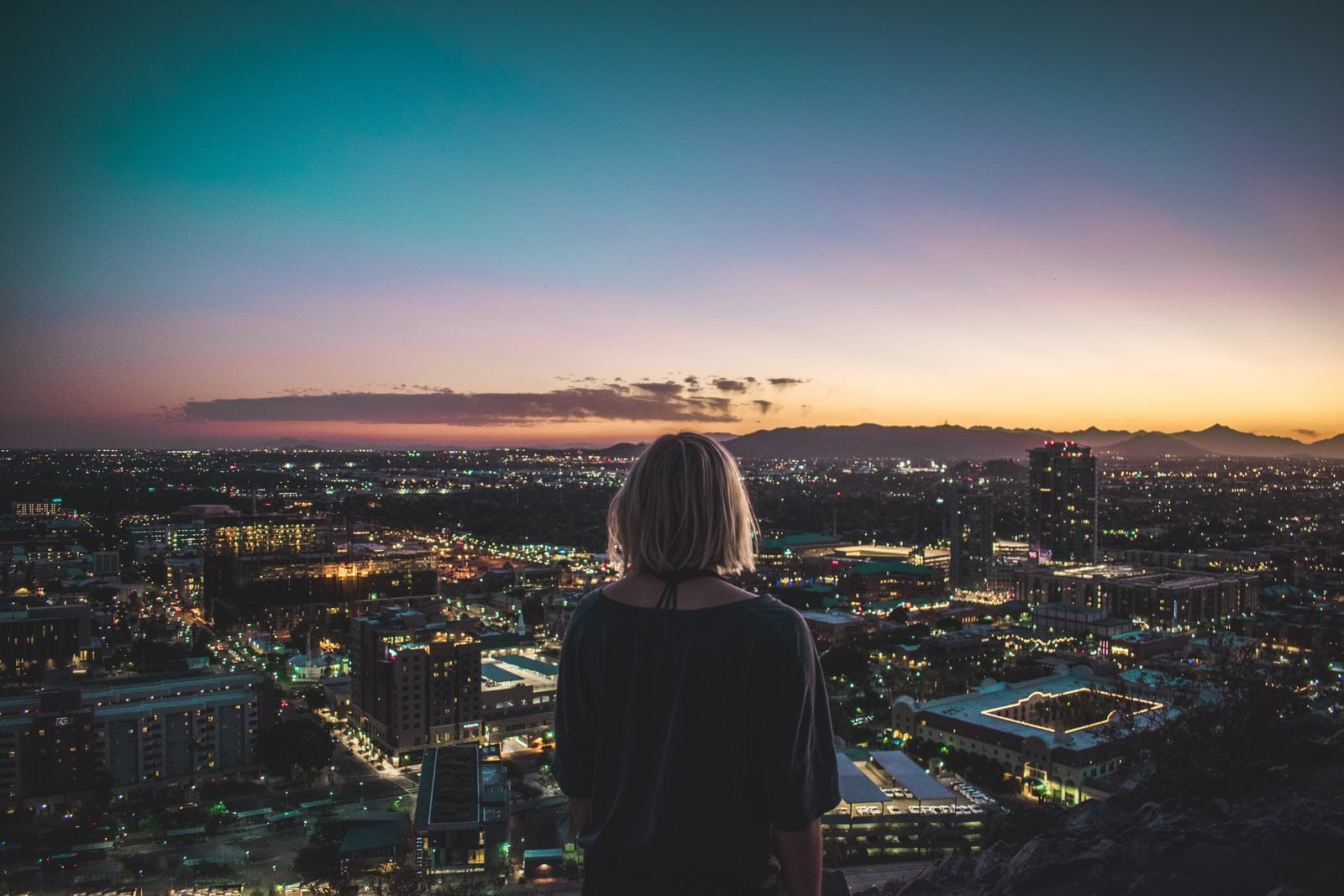 woman in black shirt standing on top of building looking at city lights during night time